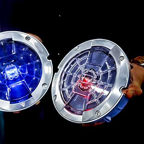 A closeup image of two smart road studs, which can monitor traffic and road conditions. Each stud is circular with a metallic rim and light at its center. They appear against a dark background. An outstretched hand holds one of the studs.