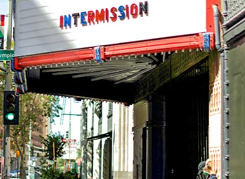 "An image of the outside of a movie theater in Los Angeles. The theater's marquee sign says ""INTERMISSION."""