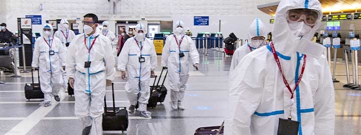 Airline crew members dressed in protective suits arrive at Los Angeles International Airport. They are masked and pulling their luggage behind them inside the airport.