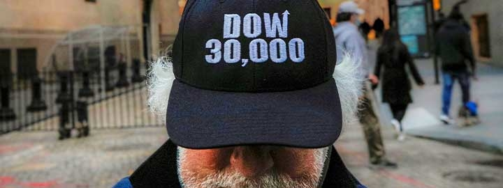 "A closeup image of a baseball cap that says ""DOW 30,000"" worn by a trader standing outside the New York Stock Exchange. The man's eyes are hidden by the bill of the cap. He has gray hair beneath the cap and a gray beard and mustache. The scene behind him is blurred and includes passersby."