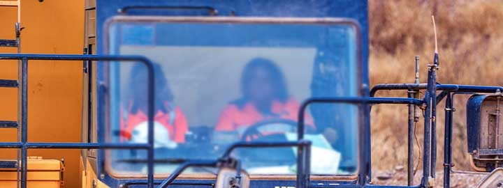 A view of the front of a truck driven by a woman working at a gold mining site in Burkina Faso. Taken through the truck's front window, the image shows the driver and her co-worker, who is in the passenger seat.