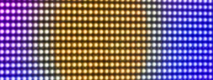 This close-up image of an LED display along Wembley Way in London shows rows of small circles of brightly colored lights. The colors form a pattern that resembles the sun at the center, surrounded by hazy glow that is, in turn, surrounded by cooler-toned lights that resemble the sky.