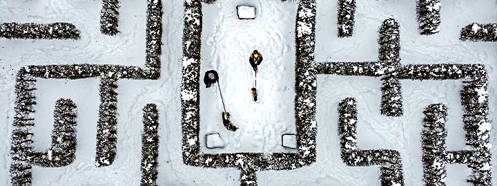 This is an aerial view of a snow covered garden maze in Gelsenkirchen, Germany. Two people walking dogs are at the center of the maze. The center is surrounded by  snow-covered pathways bordered by shrubbery.