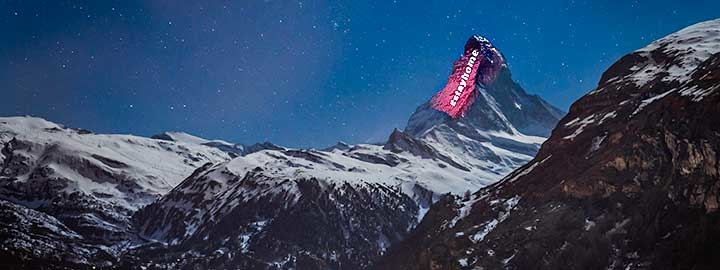 "A nighttime image shows the lights of Zermatt, Switzerland in the foreground. Beyond Zermatt, the alps rise. The Matterhorn is illuminated by a light installation meant to foster hope during COVID-19. The message projected on the mountain says ""#StayHome""."