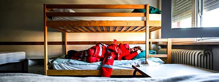 A photo of a Red Cross volunteer resting on a bottom bunk in a dormitory during Easter Sunday at the organization's headquarters in Turin, Italy.