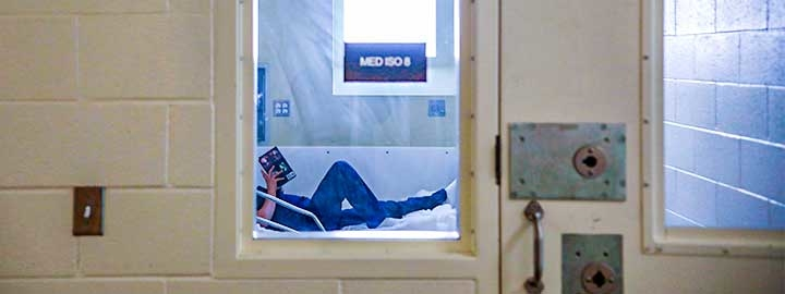 A photo of an inmate reading a book on a bed in the infirmary of a women's prison in California.