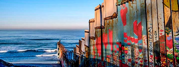 A photo of the US-Mexico border fencing at Playas de Tijuana, Mexico, running down a hill to the Pacific Ocean. The fence is made of rusted, patchy metal and covered with graffiti.